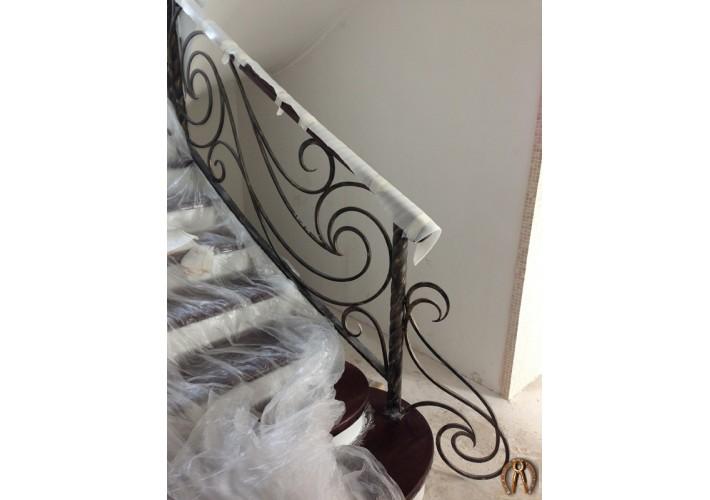 Радиусная лестница с бетонным основанием, ступени из массива, кованые перила