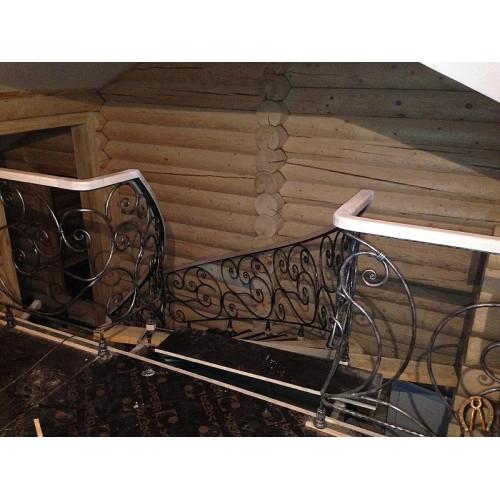 Лестница с коваными радиусными перилами в деревянном доме